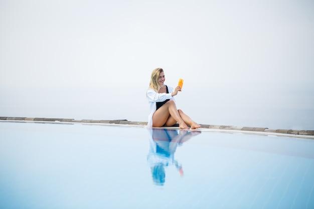Młoda piękna kobieta w stroju kąpielowym siedzi przy basenie i smaruje skórę kremem przeciwsłonecznym. pielęgnacja skóry latem. zdjęcie wysokiej jakości