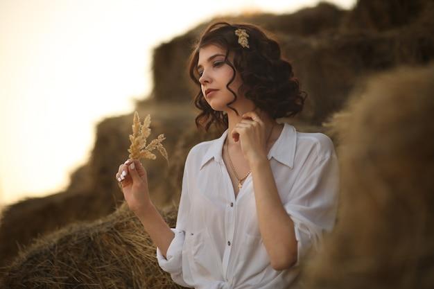 Młoda piękna kobieta w stylu rustykalnym siedzi na wsi