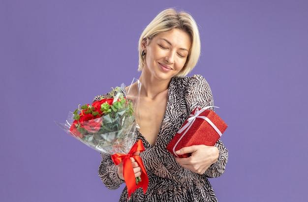 Młoda piękna kobieta w sukience trzymająca prezent i bukiet czerwonych róż szczęśliwa i zadowolona uśmiechnięta z zamkniętymi oczami koncepcja walentynki stojąca nad fioletową ścianą