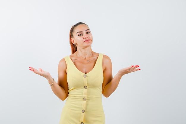 Młoda piękna kobieta w sukni pokazując bezradny gest i patrząc zdziwiony, widok z przodu.