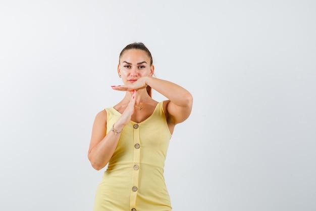 Młoda piękna kobieta w sukni pokazując gest przerwy i patrząc pewnie, widok z przodu.