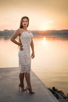 Młoda piękna kobieta w sukni pozowanie na wybrzeżu morza o zachodzie słońca