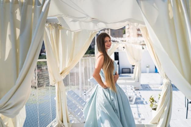 Młoda piękna kobieta w sukni stojącej na molo