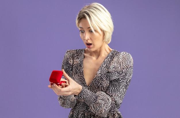 Młoda piękna kobieta w sukni trzyma czerwone pudełko z pierścionkiem zaręczynowym patrząc na to zdumiony i zaskoczony koncepcja walentynki stojąca nad fioletową ścianą