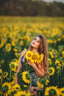 Młoda piękna kobieta w sukni wśród kwitnących słoneczników. kultura rolna.