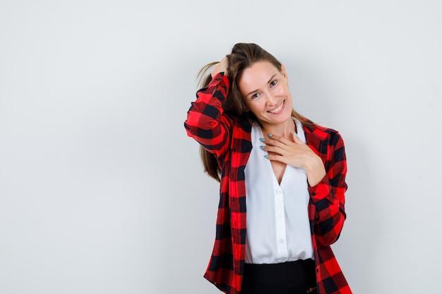 Młoda piękna kobieta w swobodnym stroju trzymając rękę za głową, z ręką na klatce piersiowej i patrząc wesoło, widok z przodu.