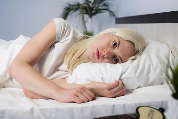 Młoda piękna kobieta w sypialni w domu, leżąc w łóżku późno w nocy, próbując zasnąć cierpiącej na bezsenność