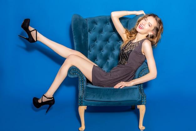 Młoda piękna kobieta w szarej sukience siedzi na niebieskim fotelu
