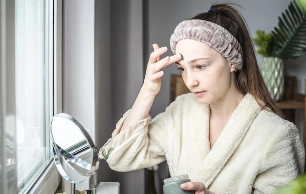 Młoda piękna kobieta w szlafroku kąpielowym nakłada na twarz zieloną maskę kosmetyczną