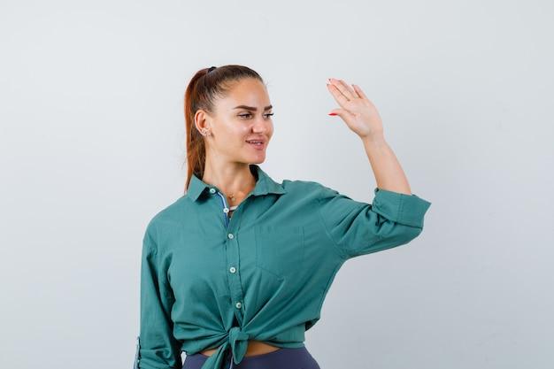 Młoda piękna kobieta w zielonej koszuli machając ręką na powitanie i patrząc wesoły, widok z przodu.