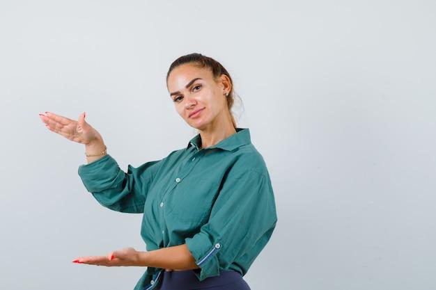 Młoda piękna kobieta w zielonej koszuli pokazując znak rozmiaru i patrząc radosny, widok z przodu.