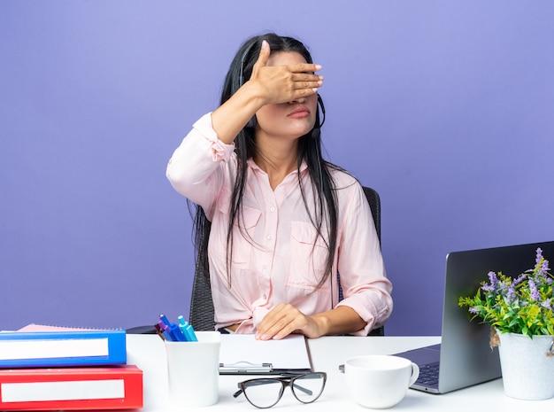 Młoda piękna kobieta w zwykłych ubraniach nosząca zestaw słuchawkowy z mikrofonem zakrywającym oczy ręką siedzącą przy stole z laptopem na niebieskiej ścianie, pracująca w biurze