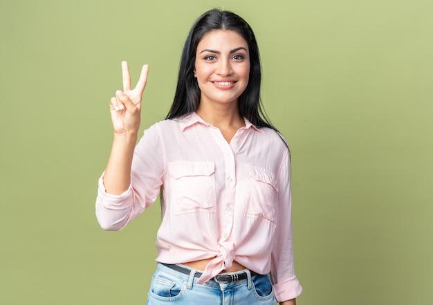 Młoda piękna kobieta w zwykłych ubraniach, patrząc z przodu, uśmiechając się radośnie pokazując numer dwa z palcami stojącymi nad zieloną ścianą