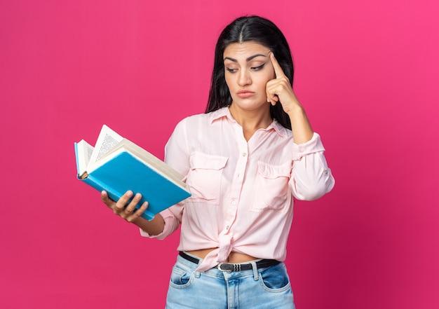 Młoda piękna kobieta w zwykłych ubraniach trzyma książkę, patrząc na nią, zdziwiona palcem na świątyni stojącej na różowo