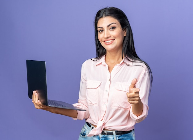 Młoda piękna kobieta w zwykłych ubraniach trzyma laptopa wskazując palcem wskazującym, uśmiechając się radośnie, stojąc na niebiesko