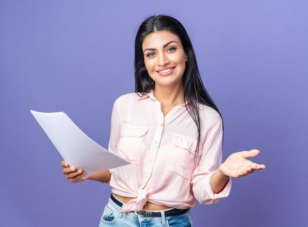 Młoda piękna kobieta w zwykłych ubraniach trzymająca dokumenty wykonujące powitalny gest ręką uśmiechniętą przyjazną stojącą nad niebieską ścianą
