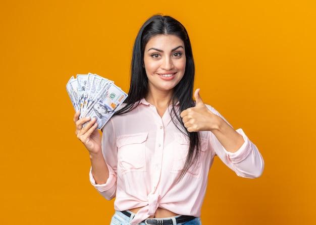 Młoda piękna kobieta w zwykłych ubraniach trzymająca gotówkę uśmiechająca się radośnie pokazując kciuk do góry stojąca nad pomarańczową ścianą
