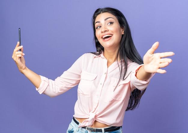 Młoda piękna kobieta w zwykłych ubraniach trzymająca smartfona patrzącego na bok szczęśliwa i wesoła, wykonująca powitalny gest ręką stojącą nad niebieską ścianą