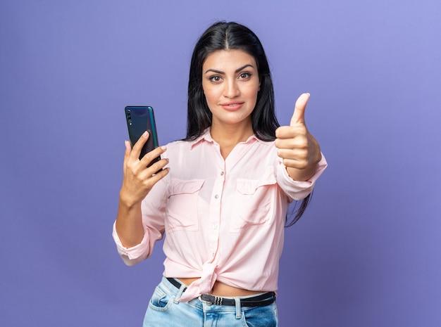 Młoda piękna kobieta w zwykłych ubraniach trzymająca smartfona wygląda na szczęśliwą i pewną siebie pokazując kciuk do góry uśmiechnięty