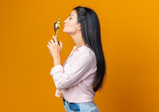 Młoda piękna kobieta w zwykłych ubraniach trzymająca trofeum całująca go szczęśliwa i pewna siebie stojąca bokiem na pomarańczowo