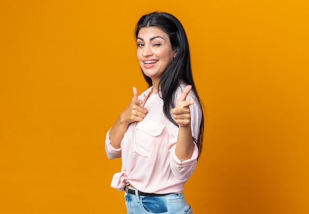 Młoda piękna kobieta w zwykłych ubraniach uśmiecha się pewnie, szczęśliwie i radośnie, wskazując palcami wskazującymi z przodu, stojąc nad pomarańczową ścianą
