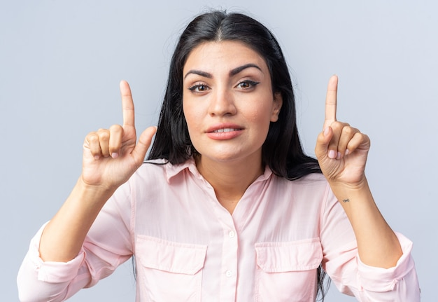 Młoda piękna kobieta w zwykłych ubraniach uśmiecha się pewnie wskazując palcami wskazującymi w górę stojąc nad białą ścianą