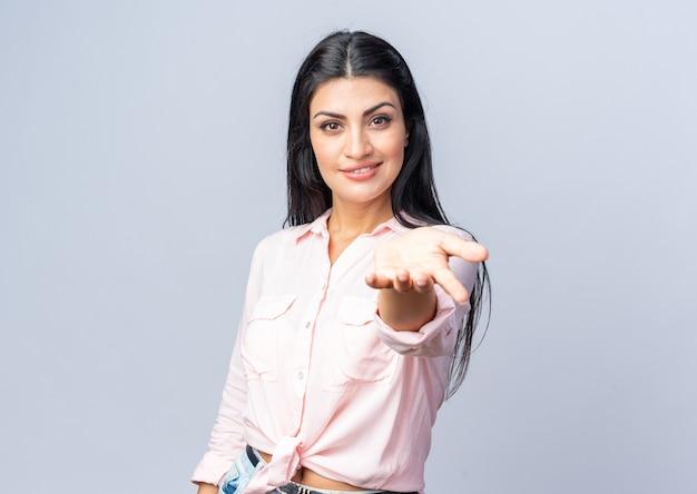 Młoda piękna kobieta w zwykłych ubraniach wygląda na uśmiechniętą pewnie, robiąc tu gest ręką