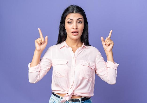 Młoda piękna kobieta w zwykłych ubraniach zaskoczona, wskazując palcami wskazującymi w górę, stojąc nad niebieską ścianą