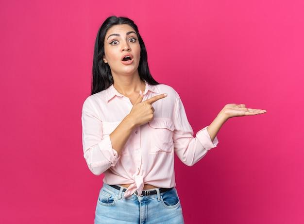 Młoda piękna kobieta w zwykłych ubraniach zaskoczyła wskazując palcem wskazującym w bok, prezentując coś ramieniem dłoni stojącej na różowo