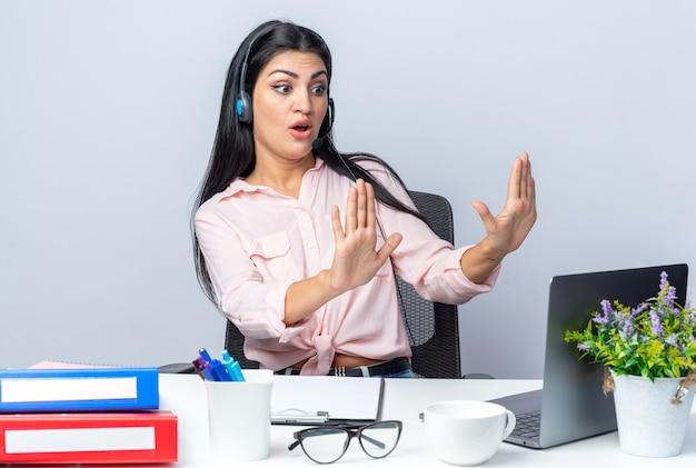 Młoda piękna kobieta w zwykłych ubraniach ze słuchawkami i mikrofonem siedzi przy stole z laptopem, patrząc na ekran, zmartwiona i zdezorientowana nad białą ścianą pracy w biurze