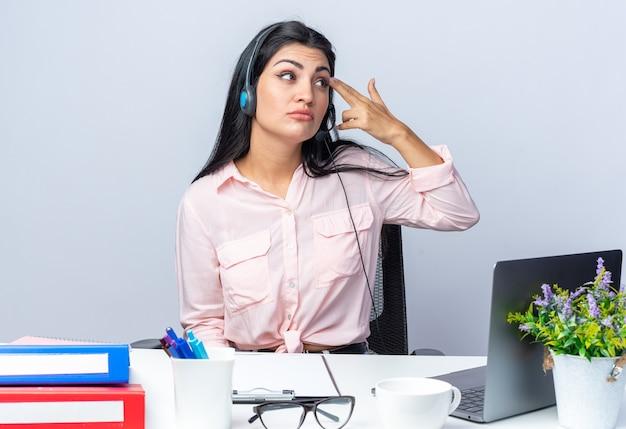 Młoda piękna kobieta w zwykłych ubraniach ze słuchawkami i mikrofonem siedzi przy stole z laptopem patrząc zdziwiona, wskazując palcami na jej skroń na białym