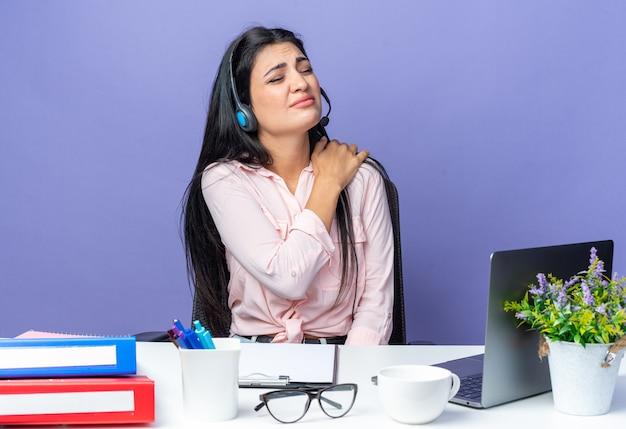 Młoda piękna kobieta w zwykłych ubraniach ze słuchawkami i mikrofonem wygląda źle, dotykając bólu ramienia, siedząc przy stole z laptopem nad niebieską ścianą, pracując w biurze
