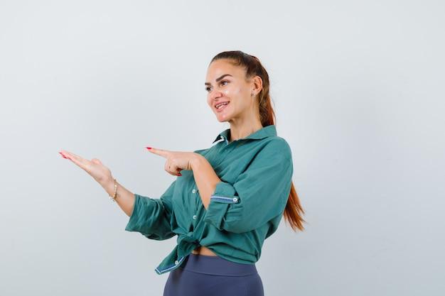 Młoda piękna kobieta wskazując w lewo, jednocześnie rozkładając dłoń w zielonej koszuli i patrząc wesoło. przedni widok.