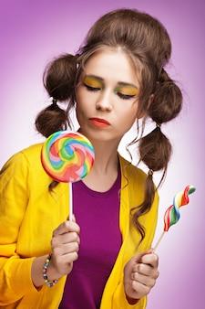 Młoda piękna kobieta wybiera co kolorowy lizak do jedzenia