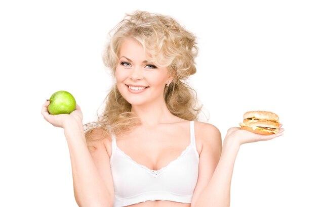 Młoda piękna kobieta wybiera między burgerem i jabłkiem.