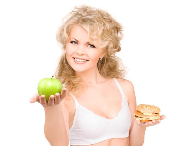 Młoda piękna kobieta wybiera między burgerem i jabłkiem