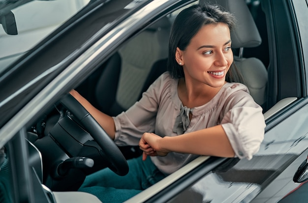 Młoda piękna kobieta wybiera nowy pojazd w salonie samochodowym. pani w salonie samochodowym. kobieta kupuje samochód.