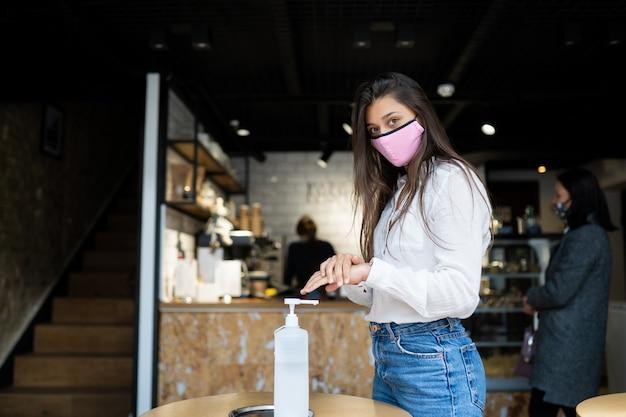 Młoda piękna kobieta z atrakcyjnym uśmiechem w masce ochronnej za pomocą żelu do dezynfekcji rąk do mycia rąk.