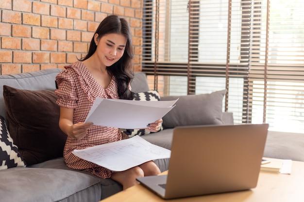Młoda piękna kobieta z azji patrząc na swoje plany pracy przed laptopem w swoim salonie podczas pracy w domu podczas blokady covid