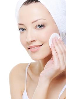 Młoda piękna kobieta z bawełnianym mopem czyści jej twarz