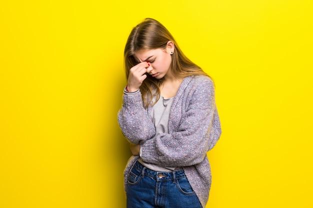 Młoda piękna kobieta z bólem głowy na białym tle.