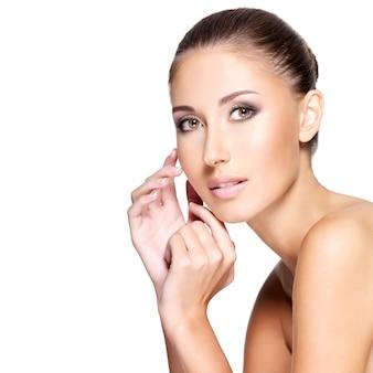 Młoda piękna kobieta z czystej zdrowej skóry dotykając jej twarzy, na białym tle.