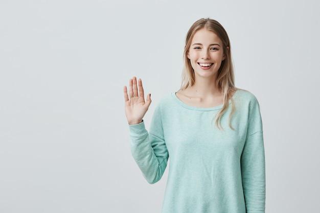 Młoda piękna kobieta z długimi blond włosami, mówiąc: cześć
