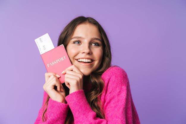 Młoda piękna kobieta z długimi brązowymi włosami trzymająca paszport i bilet podróżny na białym tle