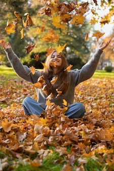 Młoda piękna kobieta z długimi naturalnymi włosami siedzi na ziemi i rzuca żółte liście w parku jesień