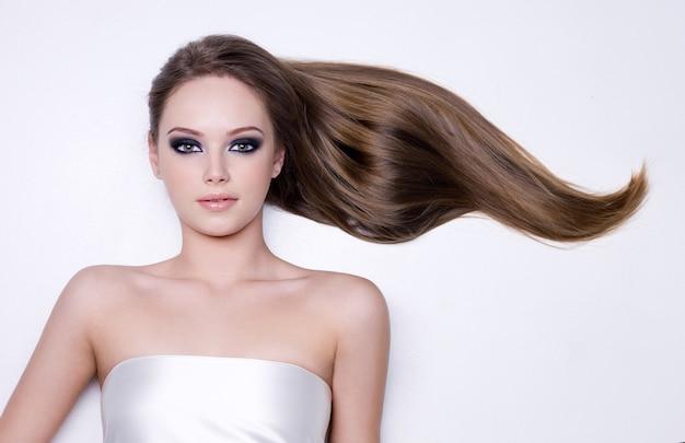 Młoda piękna kobieta z długimi prostymi gładkimi włosami - białe tło