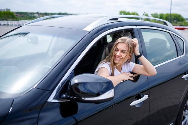 Młoda piękna kobieta z długimi włosami siedzi w czarnym samochodzie na parkingu. ładna dziewczyna w ubraniu. podróż samochodem