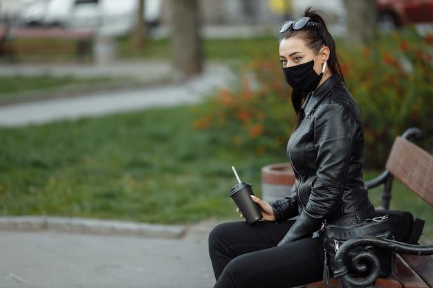 Młoda piękna kobieta z filiżanką kawy na sobie czarną maskę medyczną.