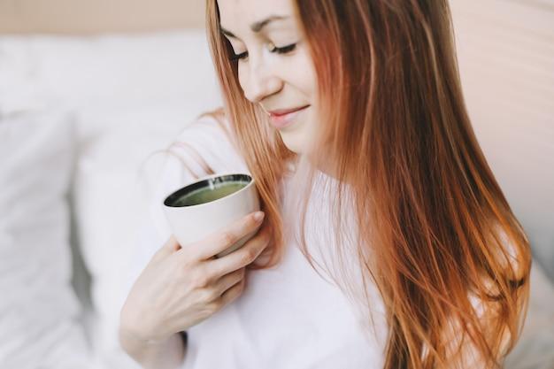 Młoda piękna kobieta z filiżanką kawy w łóżku w domu