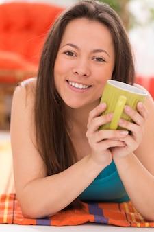 Młoda piękna kobieta z herbacianym kubkiem
